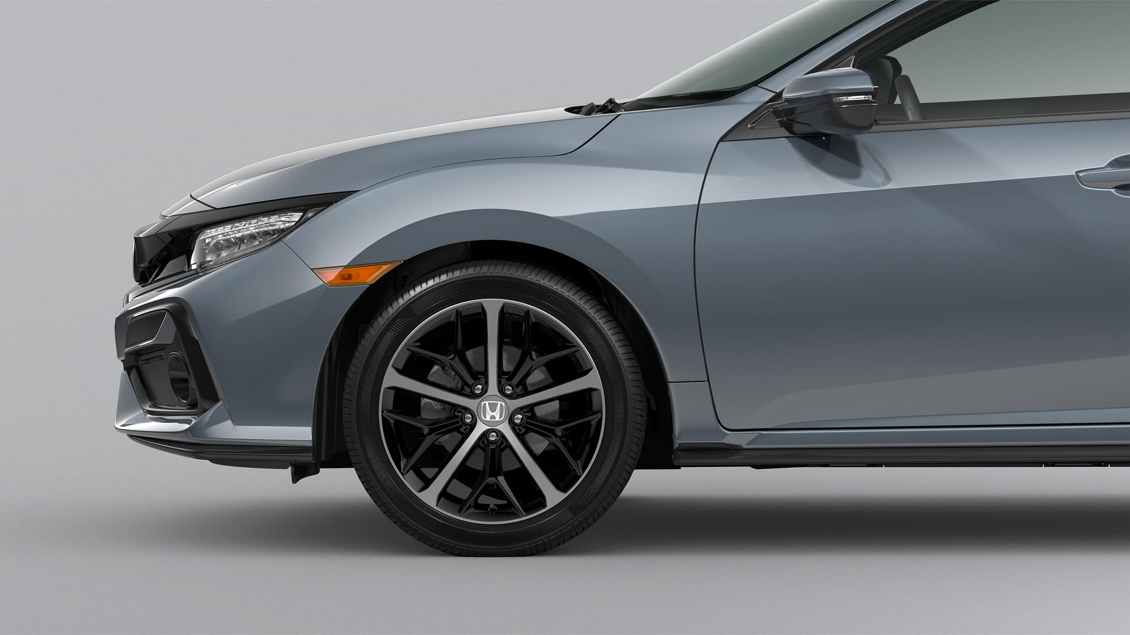 Front passenger-side 18-inch alloy wheel detail on the 2021 Honda Civic Sport Touring Hatchback in Sonic Gray Pearl.