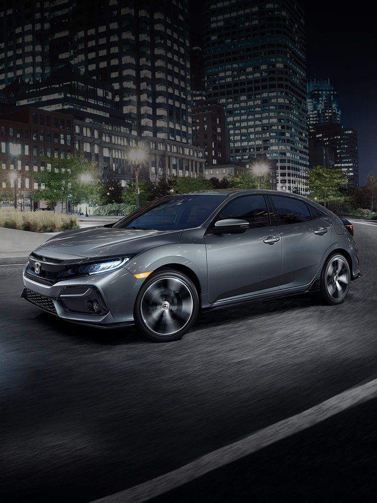 Front driver-side view of the 2021 Honda Civic Sport Touring Hatchback, in Sonic Gray Pearl, driving in city at night.