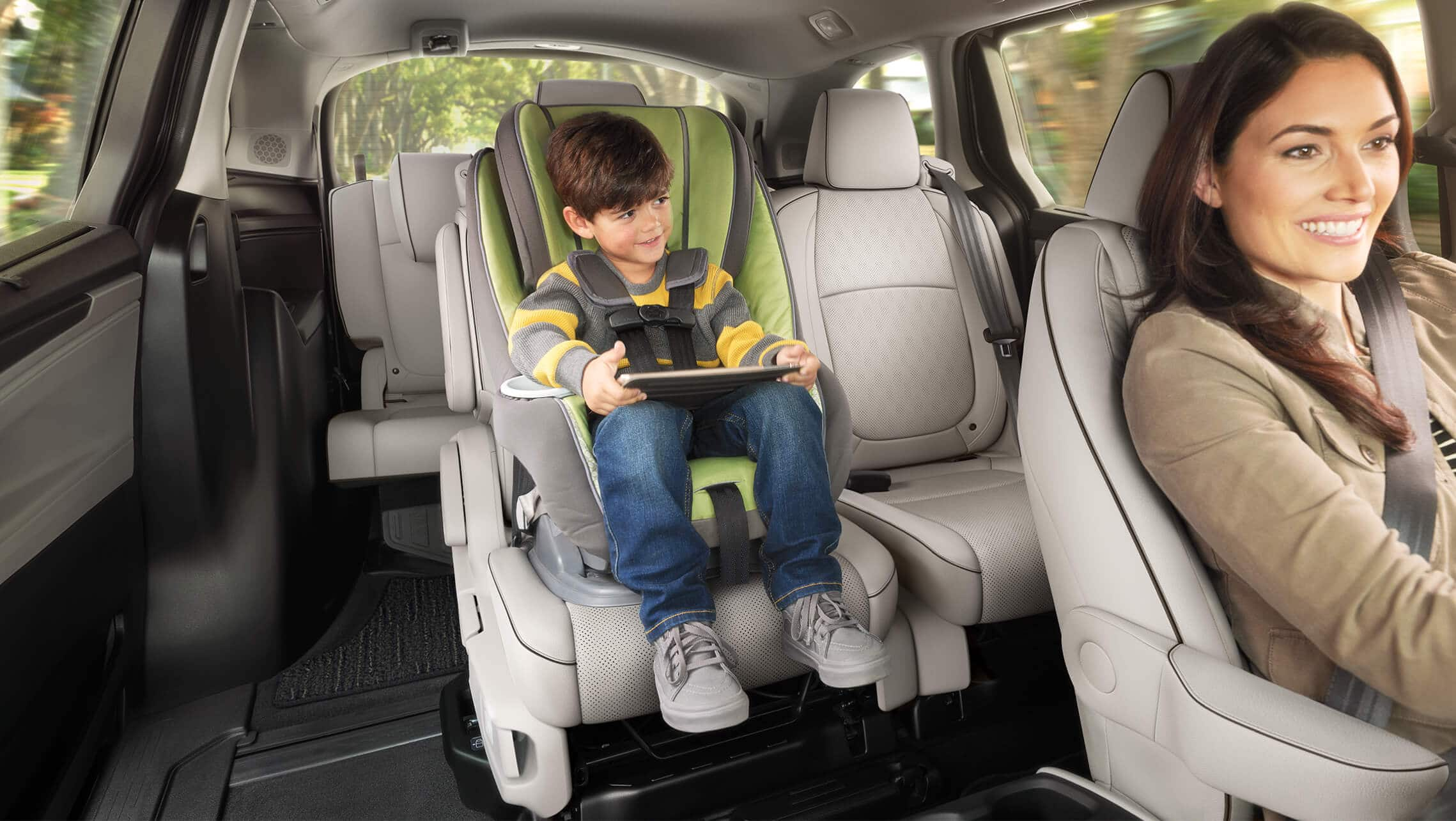 Interior view of Magic Slide® 2nd-row seats, with woman driving and child in rear car seat, in the 2021 Honda Odyssey Elite with Gray Leather.