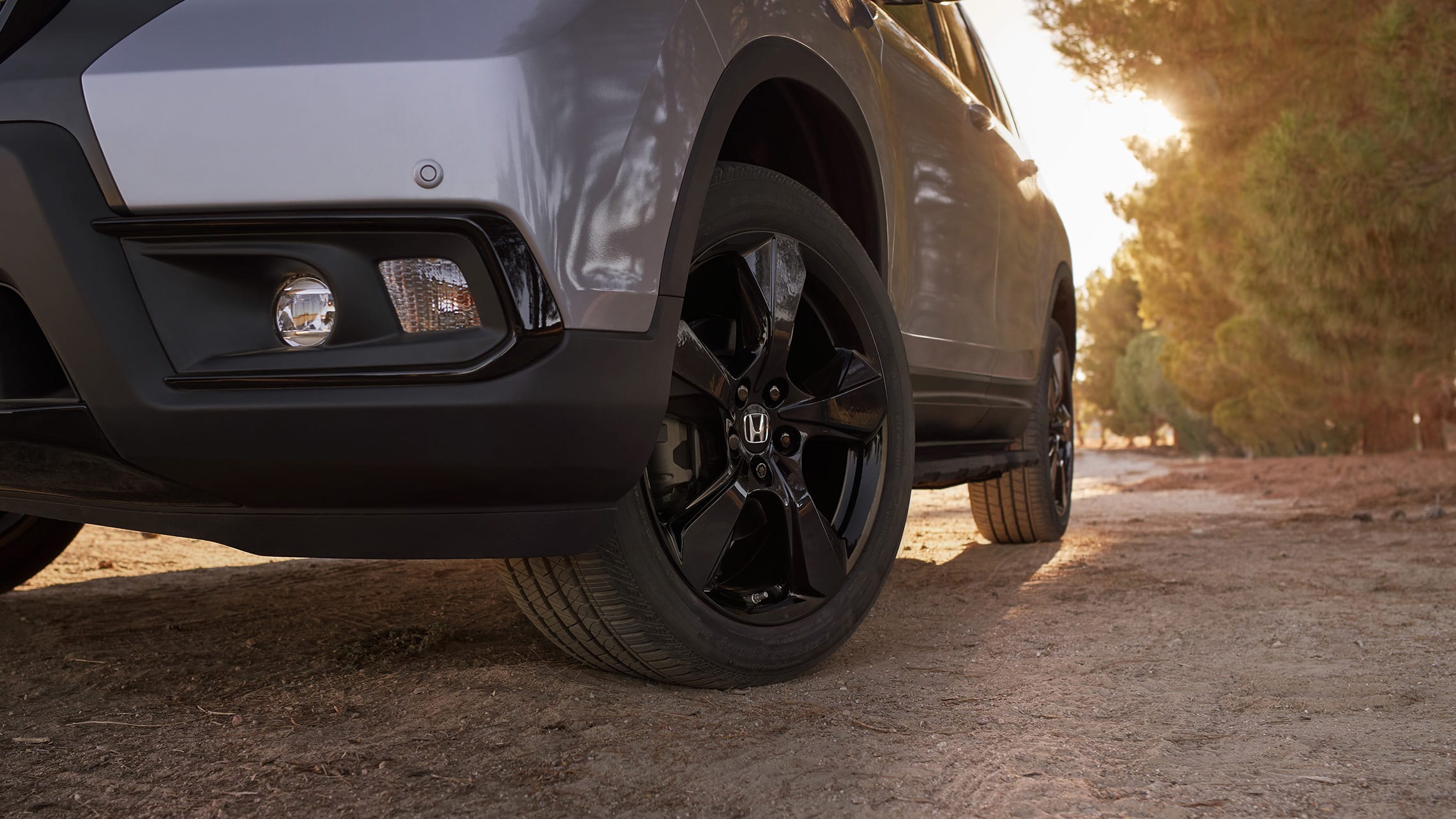 20-inch black alloy wheels on the 2021 Honda Passport Elite, in Lunar Silver Metallic with Honda Genuine Accessories, driving on a rugged road.