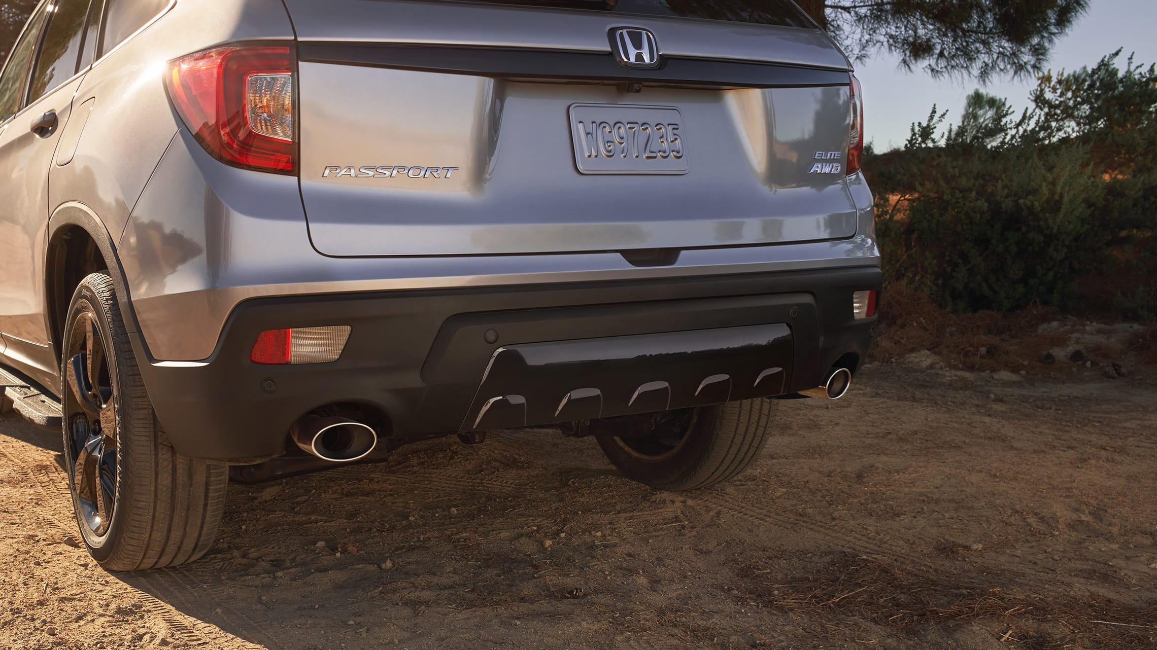 Dual exhaust finishers with parking sensors on the 2021 Honda Passport Elite in Lunar Silver Metallic.