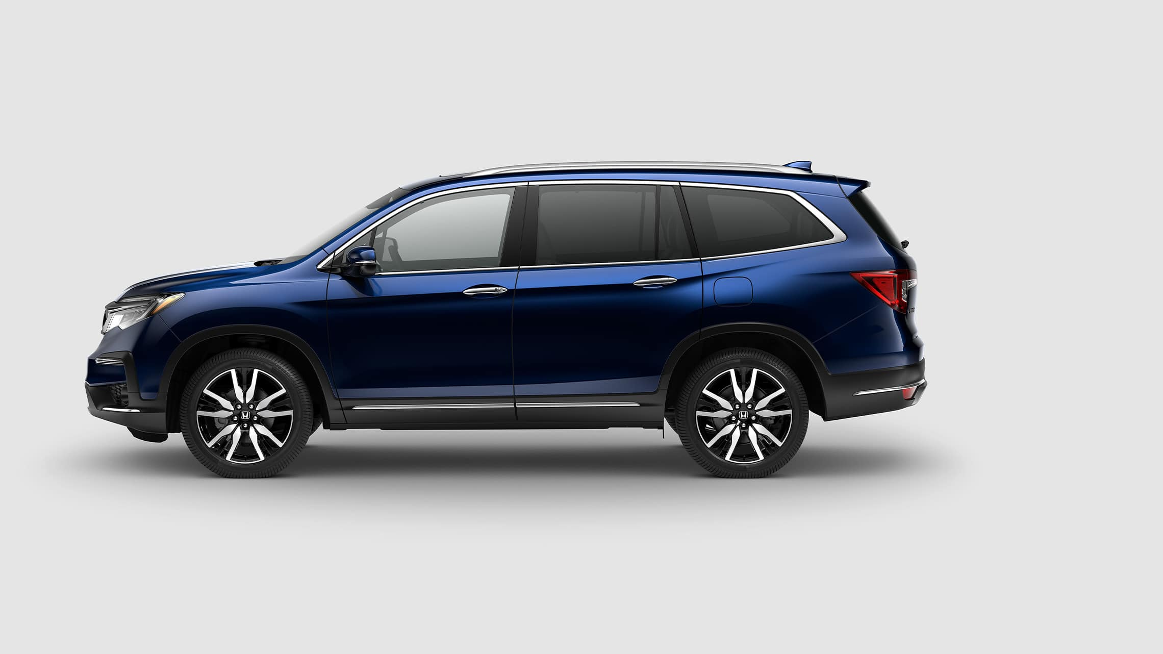 Driver-side profile of 2021 Honda Pilot Elite in Obsidian Blue Pearl.